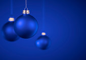 Three blue Christmas balls. Solid matt Christmas ornaments hanging against royal blue background. Christmas decoration, festive atmosphere concept. Selective focus, copy space.