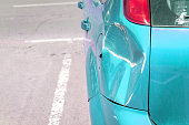 istock Light blue scratched car with damaged paint in crash accident or parking lot and dented damage of metal body from collision 1151405606