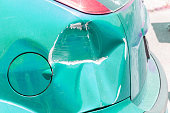 istock Light blue scratched car with damaged paint in crash accident or parking lot and dented damage of metal body from collision 1151556972