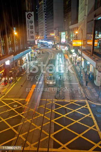 istock Light blur motion scene of tram and traffic in central Hong Kong at night. There are many pedestrians on the street. 1128802171