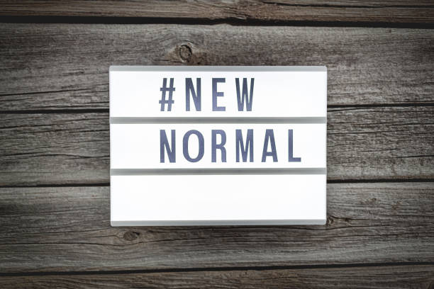 light box signs with text hashtag #new normal on wooden table. new normal concept. social distancing. - new normal foto e immagini stock