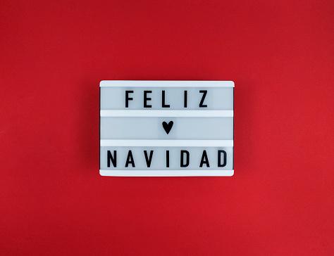 Light box with Feliz Navidad phrase, Spanish Merry Christmas on a red background.