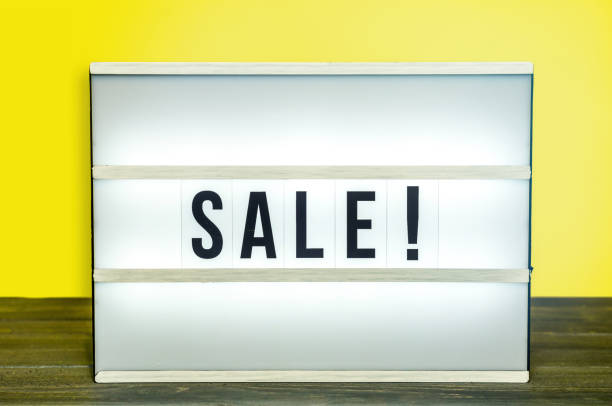 Light box with Sale letters against yellow background on wooden table stock photo