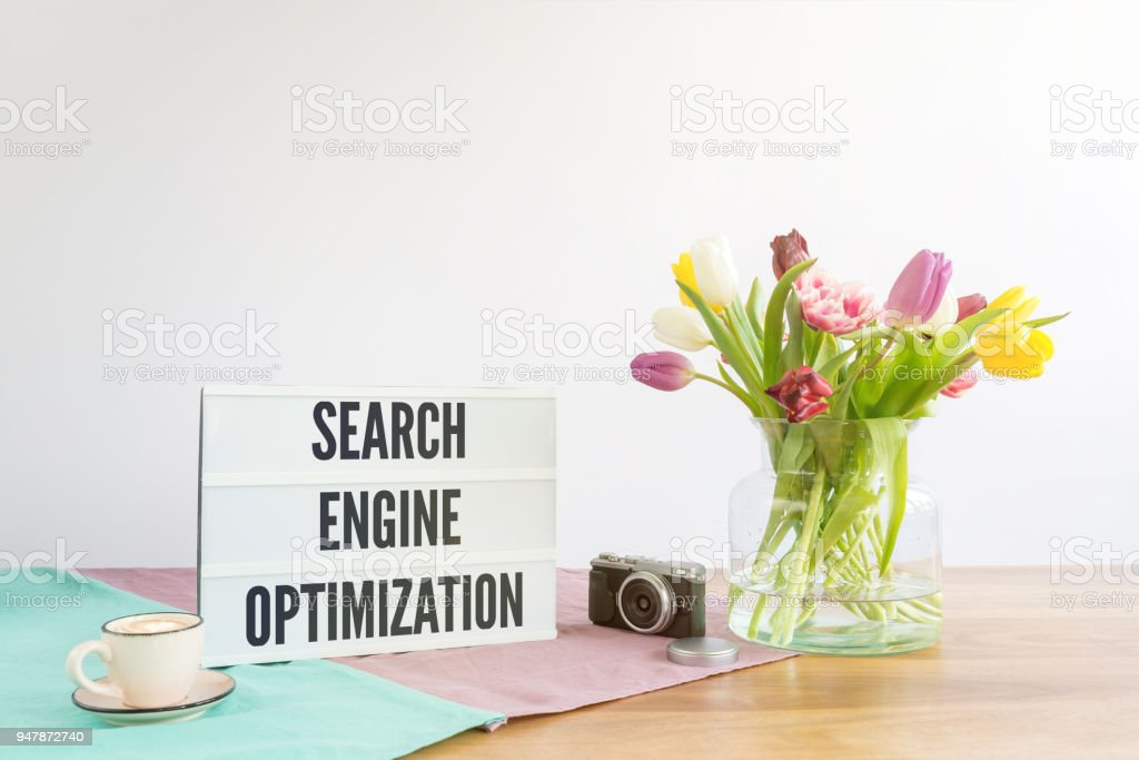 Light box with search engine optimization writing on wooden desk with white background stock photo