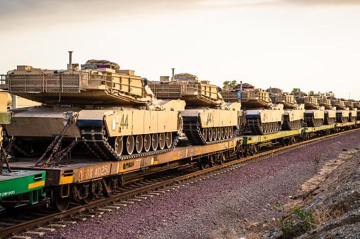 Light Brown Combat Ftrac 120mm Gun Tanks in Transport on Rail Train In Line with Blue Sky for War Defense Artillery