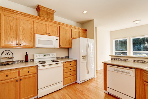 Light Brown Kitchen Cabinets And White Appliances Stock ...
