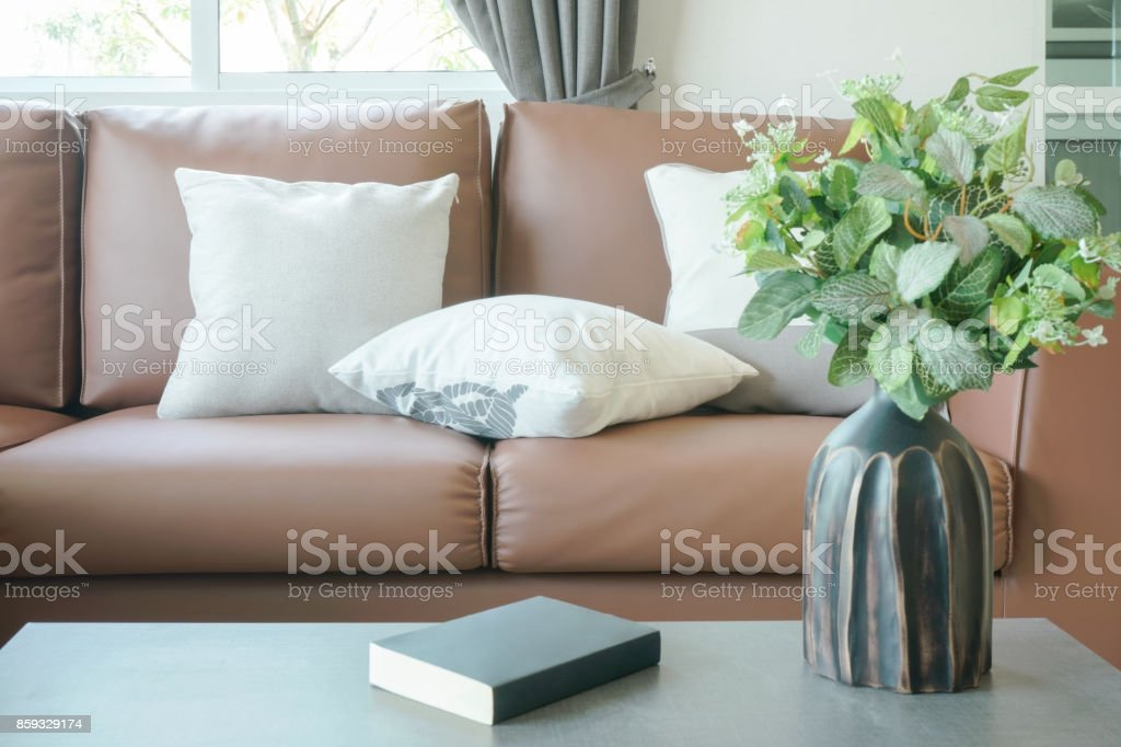 Light Brown Leather Sofa With Vase And Book On Center Table Stock