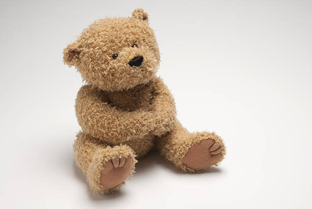 light brown stuffed bear sitting on white surface - teddy bear stock photos and pictures