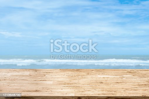 light brown wood table on blurred seascape background
