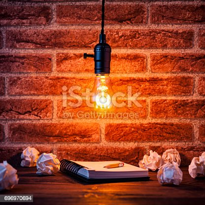 istock Light bulb and notepad on brick wall - Vintage Learning Grunge 696970694