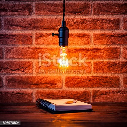 istock Light bulb and notepad on brick wall - Vintage Learning Grunge 696970804