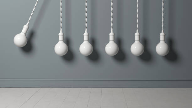 light bulb as pendulum is hitting other lightbulbs like in a newton cradle stock photo