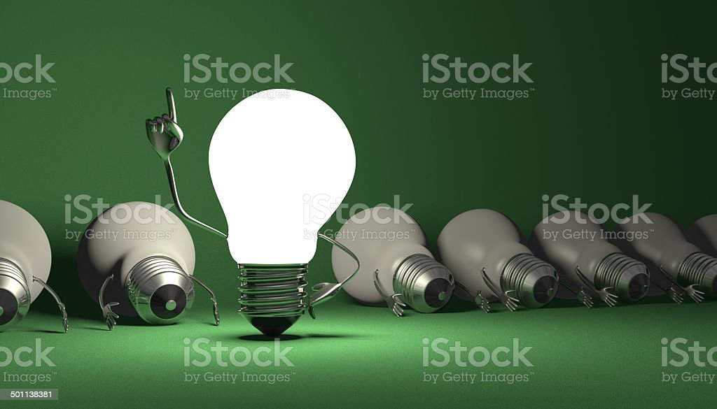 Light bulb character, aha moment  on green Glowing light bulb character in moment of insight standing among many switched off lying ones on green textured background American Heart Association Stock Photo