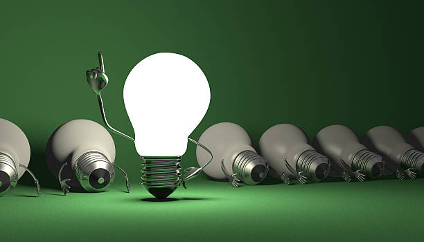 Light bulb character, aha moment  on green Glowing light bulb character in moment of insight standing among many switched off lying ones on green textured background aha stock pictures, royalty-free photos & images