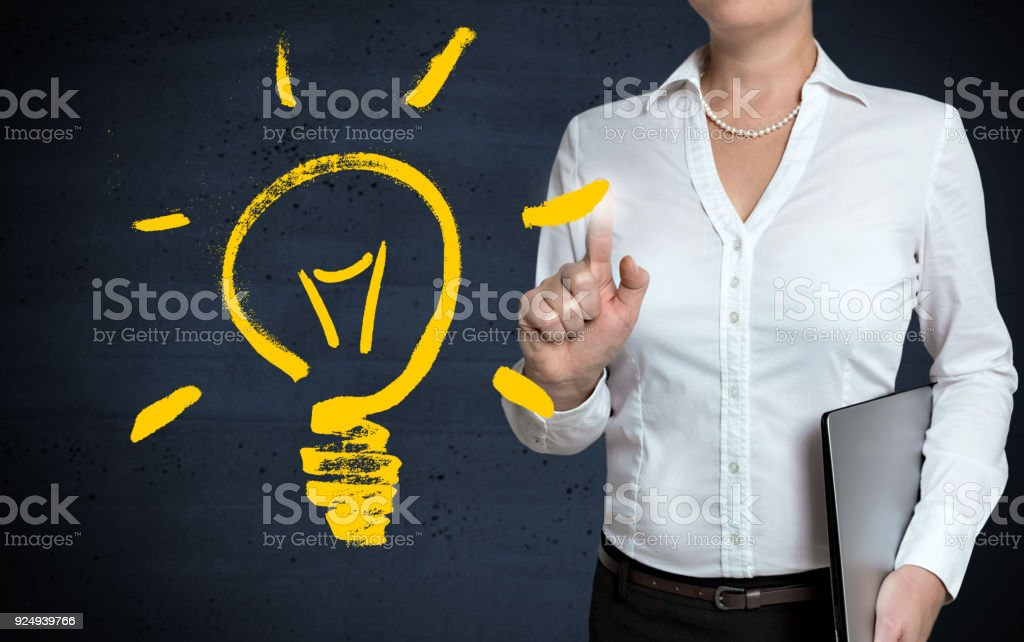 Light bulb concept touchscreen is shown by businesswoman stock photo