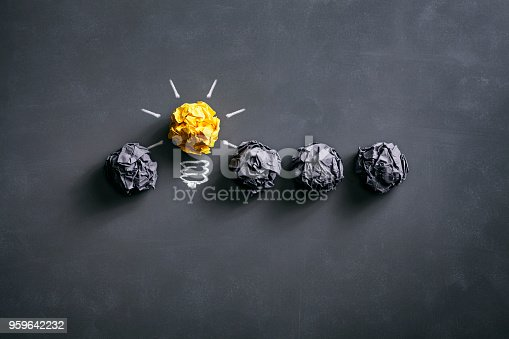 istock Light bulb crumpled paper on blackboard - Idea Concept Background 959642232