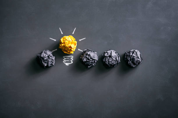 Light bulb crumpled paper on blackboard - Idea Concept Background stock photo