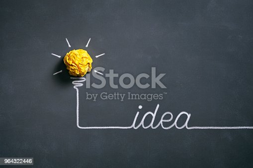 istock Light bulb crumpled paper on blackboard - Idea Concept Background 964322446