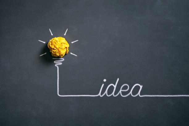 Light bulb crumpled paper on blackboard - Idea Concept Background stock photo
