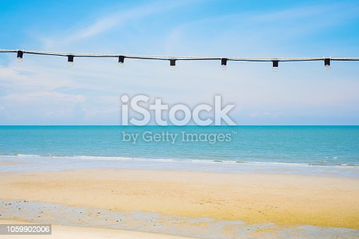 637797672 istock photo Light bulb hanging decorated with blue sky and tropical sea beach background with copy space.Beautiful nature frame idea concept. 1059902006