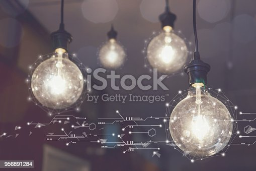 istock Light bulb hanging on the ceiling of the cafe. map network connection, concept social media diagram of growth. vintage tone 956891284
