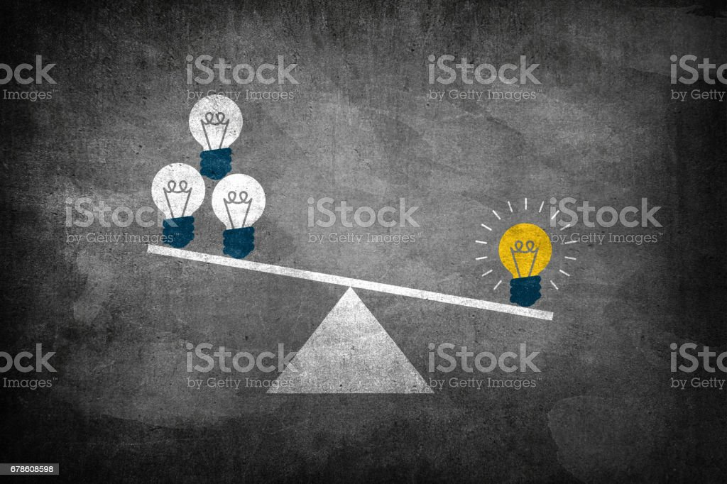 Light bulb icons on weight scale over blackboard stock photo