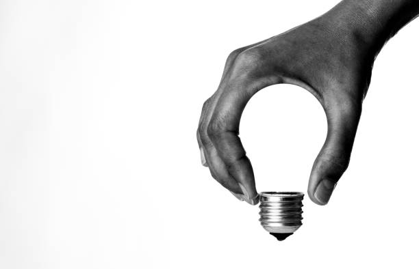 light bulb in hand - single object stock pictures, royalty-free photos & images