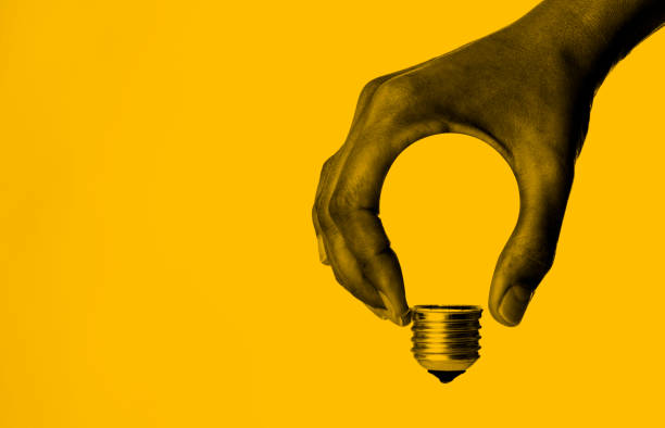 Light Bulb in Hand Light bulb in human hand, yellow background. finding stock pictures, royalty-free photos & images