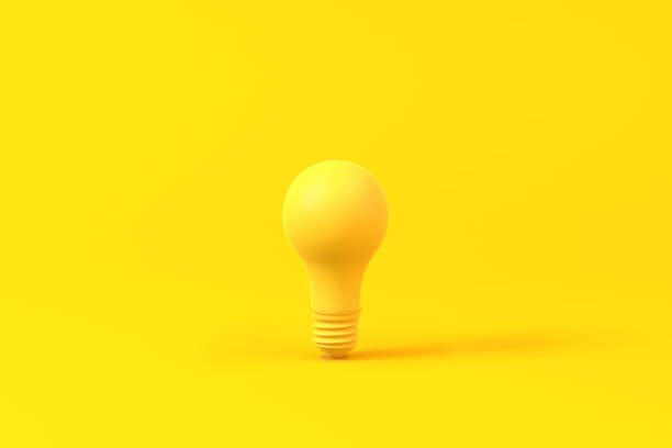 Light bulb isolated over a yellow background. Minimalist concept. stock photo