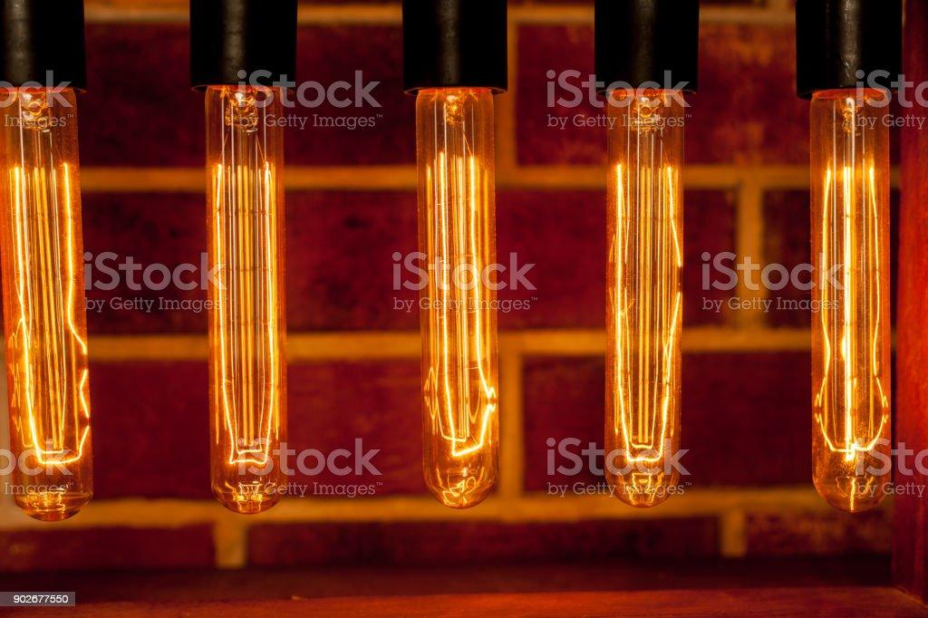 Light bulb lamp on dark red brick background with hotspot close up loft stock photo