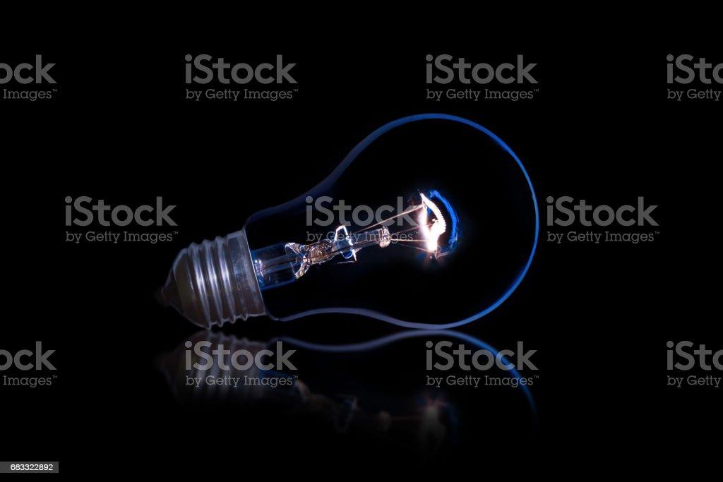 Light bulb on a black background zbiór zdjęć royalty-free