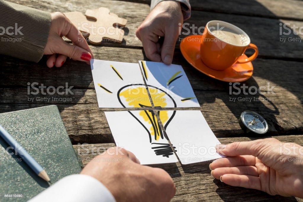 Glühbirne auf einem rustikalen Holztisch draußen in der Sonne – Foto