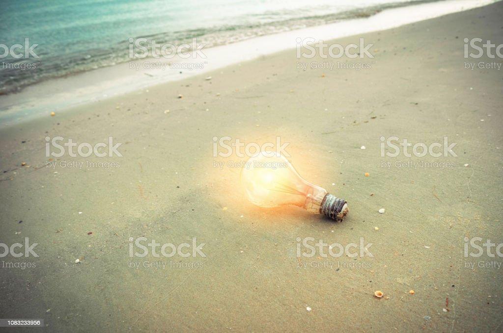 light bulb on beach / Idea concept light bulb with orange lighting on...