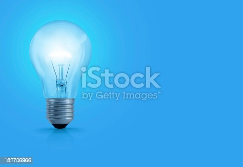 A light bulb with glowing filament on blue background.