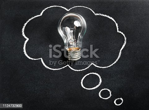 istock Light bulb on chalkboard. Thinking of new great idea. Brainstorming and creating. Creativity, innovation, inspiration and intelligence concept. Blackboard with drawn thought bubble. 1124732900