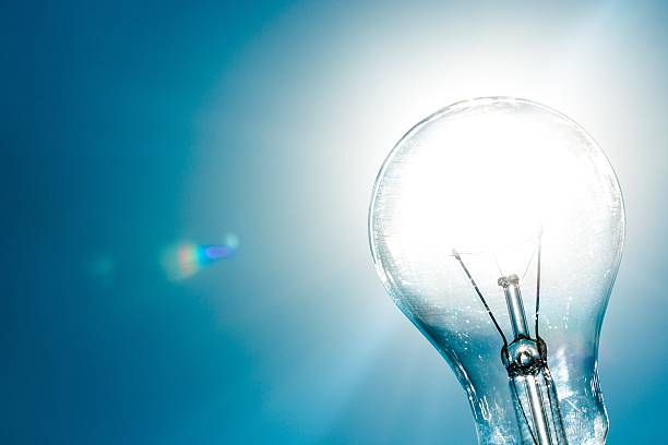 Light bulb Standard Incandescent Light Bulb on Blue Background intellectual property stock pictures, royalty-free photos & images
