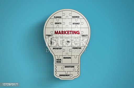 Light bulb puzzle pieces forming the word Marketing on blue background. Idea and Marketing Concept. Horizontal composition with copy space.
