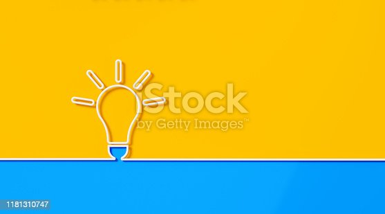White light bulb shape on yellow and blue background. Horizontal composition with copy space.