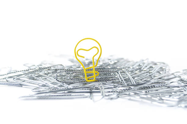 Light bulb shaped paper clip in a pile of paper clips stock photo