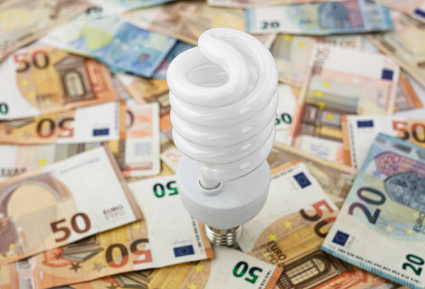 Light bulb stand up over a sheet of euro bills of twenty and fifty Metaphor about the excessive cost of light, energy and electricity, using a white halogen bulb on a bed of twenty and fifty euro bills electric light stock pictures, royalty-free photos & images
