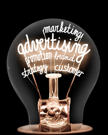 Single light bulb with shining fibers in a shape of Advertising, Strategy, Customer and Marketing concept related words isolated on black background