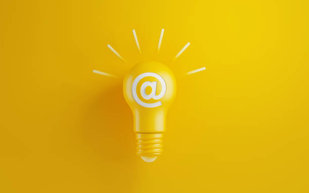 Light Bulb with At Symbol on Yellow Background Light bulb on yellow background. There is an at symbol on the lightbulb. Horizontal composition with copy space. Creativity and innovation concept. email signs stock pictures, royalty-free photos & images