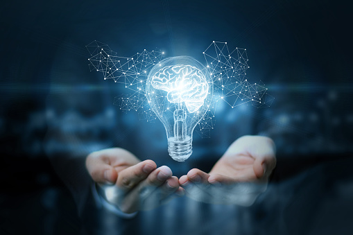 istock Light bulb with brain inside the hands of the businessman. 896358708