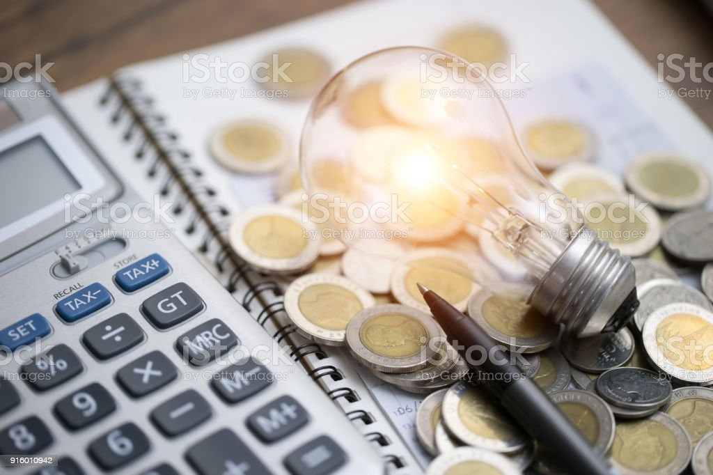 light bulb with coins and calculator on documents stock photo