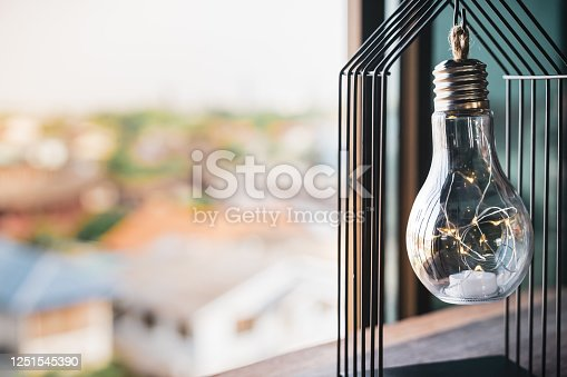 Light bulb with house cage on the table, a symbol for construction, Creative light bulb idea, power energy or business idea concept ecology, loan, mortgage, property or home.