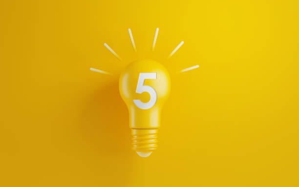 light bulb with number five on yellow background - numero 5 foto e immagini stock
