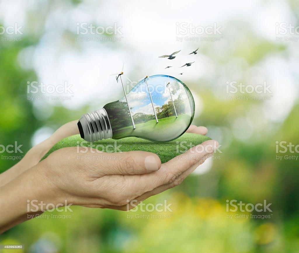 Glühbirne mit Windturbinen in in Händen, ökologische Konzept Lizenzfreies stock-foto