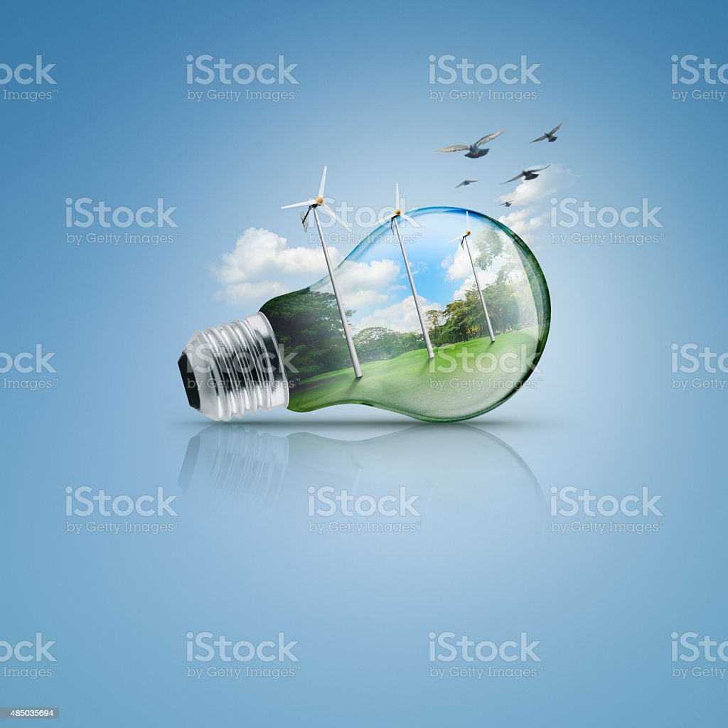 Light bulb with windmill and forest inside, Ecological concept stock photo
