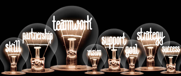 Light Bulbs Concept Photo of light bulbs group with shining fibers in a shape of Teamwork, Partnership and Collaboration concept related words isolated on black background achievement stock pictures, royalty-free photos & images
