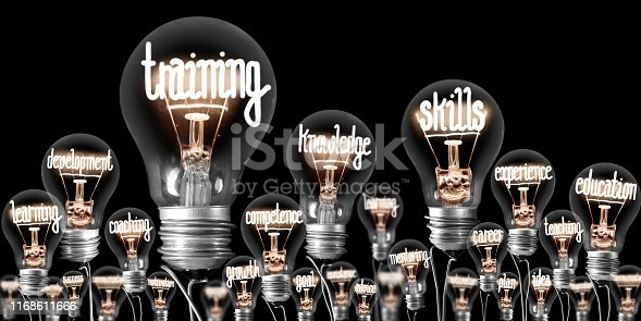 Photo of light bulbs with shining fibers in a shape of TRAINING, SKILLS and KNOWLEDGE concept related words isolated on black background